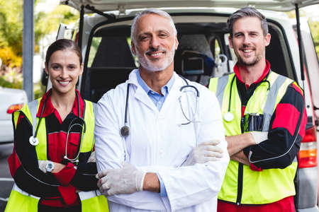 hospital trolley: Portrait of ambulance men front of ambulance car