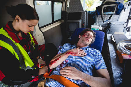 hospital trolley: Injured man with ambulancewoman in the ambulance car