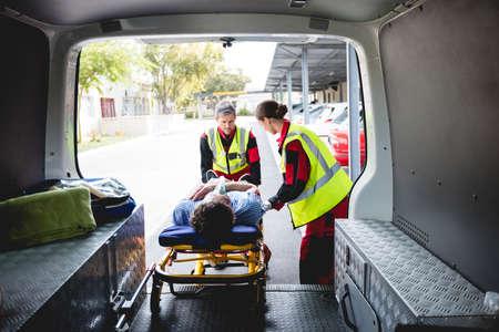 hospital trolley: Injured man with ambulance men front of ambulance car