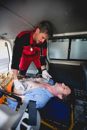 hospital trolley: Ambulance man using defibrillator in the ambulance car