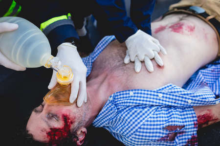 healing practitioners: Injured man being healed by a team of ambulancemen