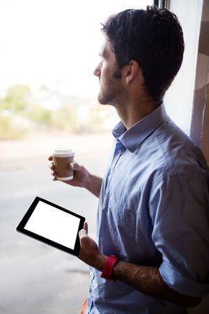 profile view: Profile view of businessman is holding a tablet and a coffee at the office