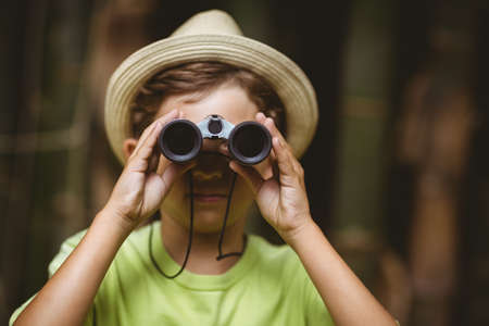 people: Young boy looking through binoculars in forest on a sunny day LANG_EVOIMAGES