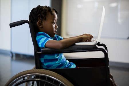 dreadlock: Disabled schoolboy on wheelchair using laptop at school