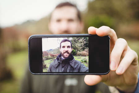 country house style: Attractive hipster man taking selfie in countryside