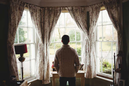 weekend activity: Rear view of hipster man looking through window in house