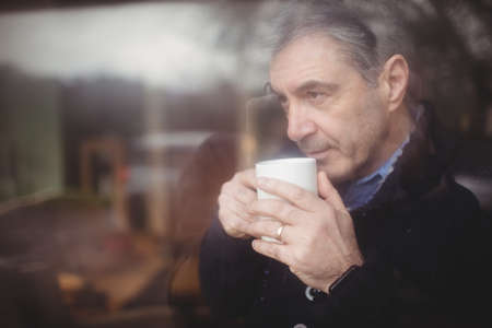 looking through window: Mature man thinking while looking through window in house LANG_EVOIMAGES