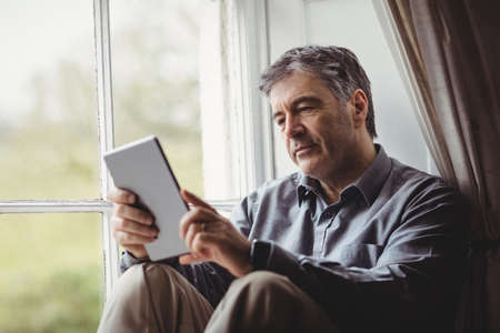weekend activity: Mature man sitting at window and using tablet computer in his house