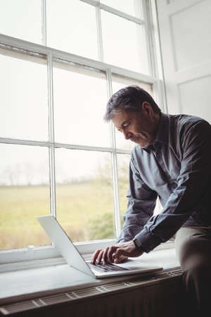 weekend activity: Mature man using laptop at window in his house