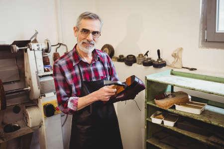 cobbler: Cobbler smiling and posing in his workshop LANG_EVOIMAGES