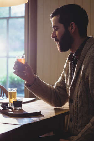 tomando refresco: Profile view of hipster man holding a shot in country house
