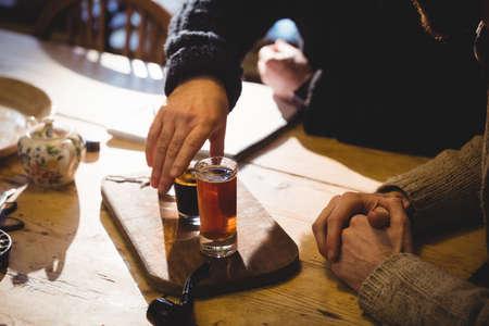 tomando refresco: Imagen cosechada de la �ltima moda y el hombre maduro que toma un disparo en casa de campo LANG_EVOIMAGES