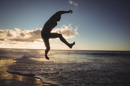 carefree: Carefree man jumping on the beach LANG_EVOIMAGES