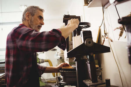 cobbler: Concentrated cobbler using machine in his workshop