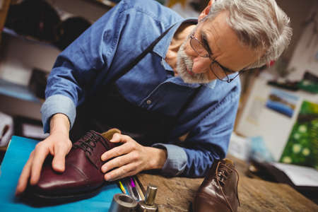 tilted: Tilted view of cobbler examining a shoe in his workshop