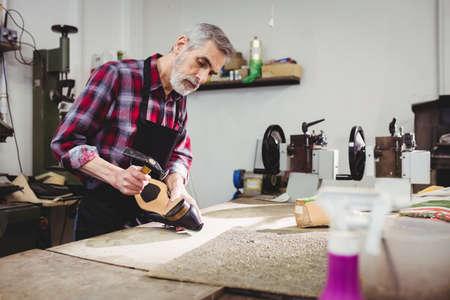 hammering: Cobbler hammering on the heel of a shoe in his workshop LANG_EVOIMAGES