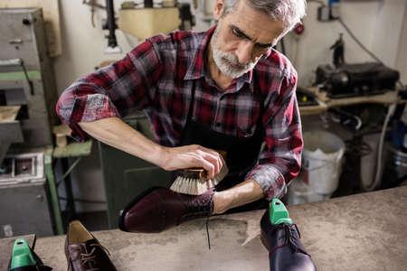 cobbler: Cobbler polishing a shoe in his workshop LANG_EVOIMAGES