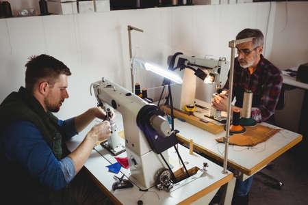 maquinas de coser: Vista de ángulo alto de zapateros uso de máquinas de coser en su taller LANG_EVOIMAGES