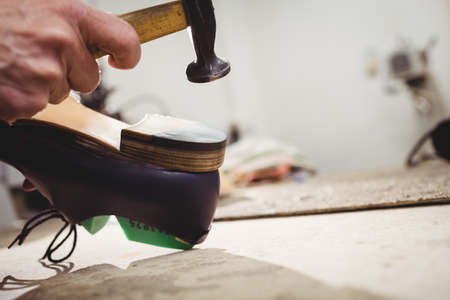 hammering: Close up of hand hammering on the heel of a shoe in a workshop LANG_EVOIMAGES