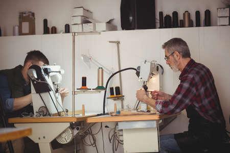 maquinas de coser: Vista de perfil de zapateros uso de máquinas de coser en su taller LANG_EVOIMAGES