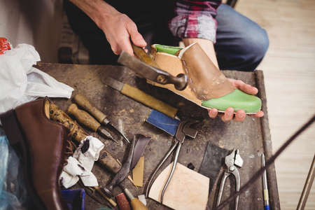 hammering: High angle view of hands hammering on a shoe in a workshop