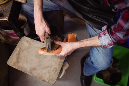 cobbler: Overhead of cobbler stapling a shoe in his workshop LANG_EVOIMAGES