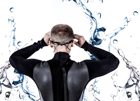bubbling: Rear view of swimmer in wetsuit wearing swimming goggles against water bubbling on white surface Stock Photo