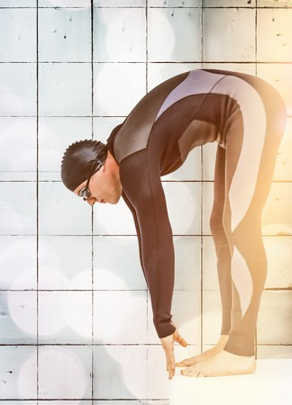 wetsuit: Swimmer in wetsuit preparing to dive against wall background