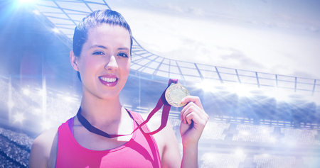 winning pitch: Portrait of sportswoman is smiling and showing her medal  against sports arena