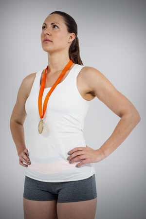 woman hands up: Athlete posing with gold medals around his neck against grey background