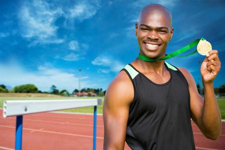 persona feliz: El hombre atlético que presenta con su medalla de oro contra frente vista de pistas de ejecución