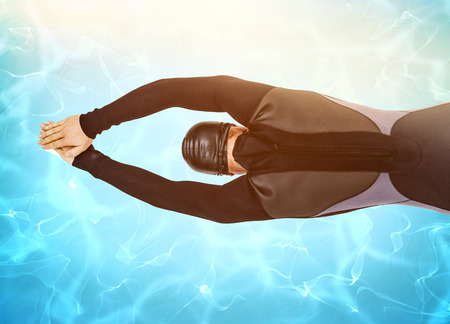 digitally: Rear view of swimmer in wetsuit while diving against blue pool under bright light Stock Photo
