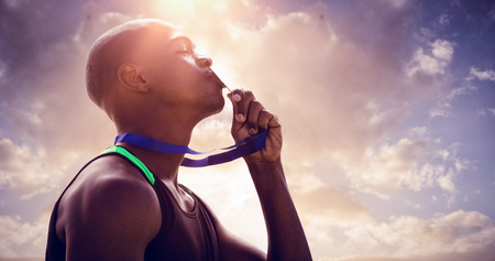 profile view: Profile view of athletic man kissing his gold medal against cloudy sky