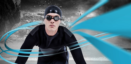 wetsuit: Confident swimmer in wetsuit against rock crashing down from cliff Stock Photo