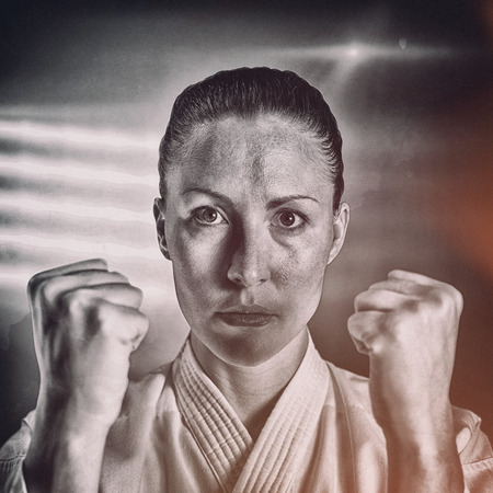 stance: Female fighter performing karate stance against spotlight