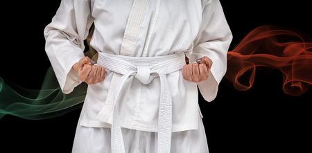karateka: Fighter performing karate stance against black background