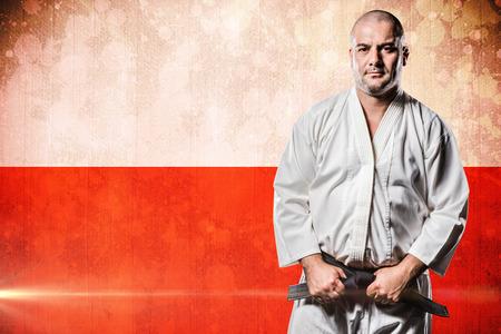 tightening: Fighter tightening karate belt against digitally generated image of polish flag