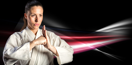 female fighter: Female fighter performing hand salute against black background Stock Photo