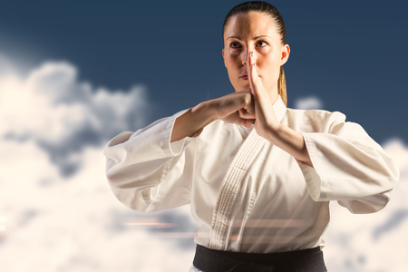 female fighter: Female fighter performing hand salute against night sky