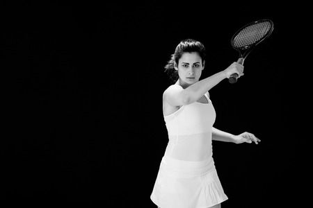 racquet: Portrait of confident female tennis player with racquet over black background