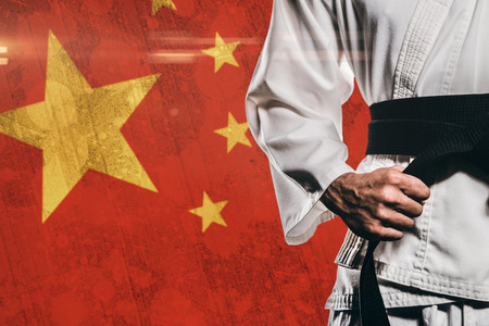 tightening: Fighter tightening karate belt against china