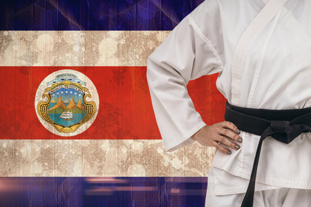 bandera de costa rica: Combatiente femenino de pie con la mano en la cadera contra la bandera de Costa Rica en efecto grunge Foto de archivo