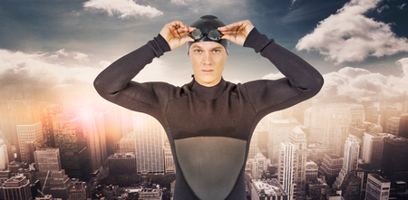 wetsuit: Swimmer in wetsuit wearing swimming goggles against aerial view of a city on a cloudy day