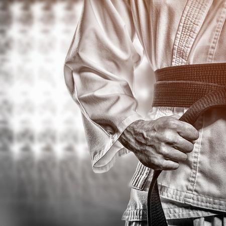 tightening: Fighter tightening karate belt against spotlights