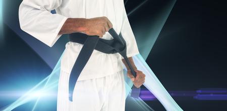 tightening: Fighter tightening karate belt against black background Stock Photo