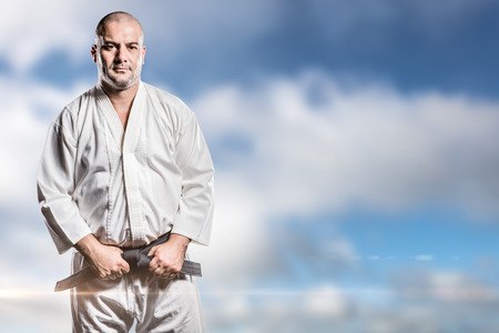 tightening: Fighter tightening karate belt against blue sky with clouds Stock Photo