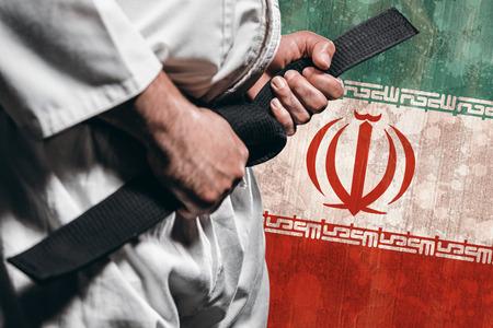 tightening: Fighter tightening karate belt against iran flag in grunge effect