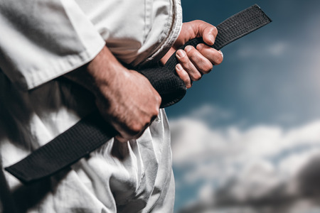 tightening: Fighter tightening karate belt against sky with clouds