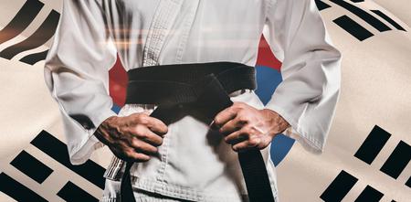 tightening: Fighter tightening karate belt against korea republic flag waving Stock Photo