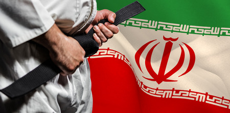 tightening: Fighter tightening karate belt against digitally generated iran national flag